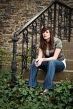 Mädchen, das auf alten Jobstepps sitzt Stockfoto