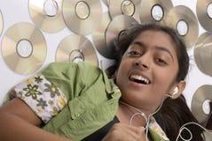 Mädchen, das auf Audiomusikcd liegt stockfotos