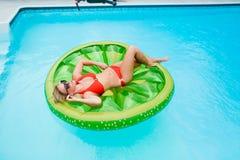 Mädchen, das auf aufblasbarem im Swimmingpool liegt lizenzfreie stockfotografie