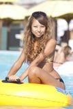 Mädchen, das auf aufblasbarem Ring auf Swimmingpool sitzt Stockfotografie