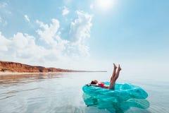 Mädchen, das auf aufblasbarem Ring auf dem Strand sich entspannt lizenzfreie stockfotografie