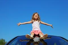 Mädchen, das auf Autodach mit den geöffneten Händen sitzt lizenzfreies stockbild