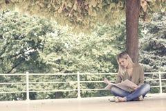 Mädchen, das auf Balkon- und Lesebuch sitzt Stockfotografie