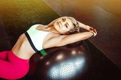 Mädchen, das auf Ball für Übung sitzt stockfoto
