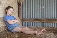 Mädchen, das auf Ballen Heu im Stall relzxing ist Stockfoto