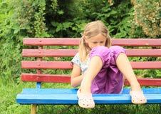 Mädchen, das auf Bank sitzt Stockfotografie
