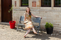 Mädchen, das auf Bank vor antikem Haus sich entspannt Lizenzfreie Stockfotografie