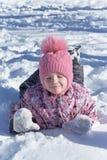 Mädchen, das auf Bauch im Schnee, Hände in der Front liegt Lizenzfreies Stockfoto