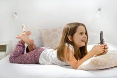Mädchen, das auf Bett mit Handy liegt Stockfoto