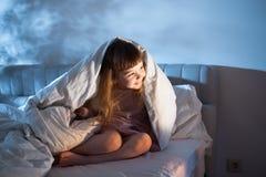 Mädchen, das auf Bett und dem Lächeln sitzt Stockfotografie