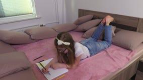 Mädchen, das auf Bett und dem Zeichnen liegt stock video
