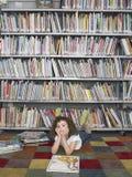 Mädchen, das auf Boden mit Märchenbuch in der Bibliothek liegt Stockfotografie