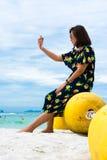 Mädchen, das auf Boje nahe Meer sitzt stockbild