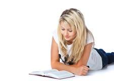 Mädchen, das auf das Fußboden- und Lesebuch legt lizenzfreies stockfoto