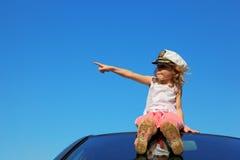 Mädchen, das auf dem Autodach darstellt durch Finger sitzt stockfotografie