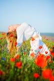 Mädchen, das auf dem Blumengebiet aufwirft Lizenzfreies Stockbild