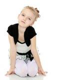 Mädchen, das auf dem Boden sich lehnt auf Händen und lächelt am Ca sitzt Lizenzfreie Stockbilder