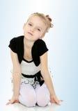 Mädchen, das auf dem Boden sich lehnt auf Händen und lächelt am Ca sitzt Lizenzfreies Stockbild