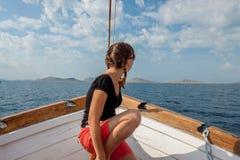Mädchen, das auf dem Bogen des Schiffs sitzt Lizenzfreie Stockbilder