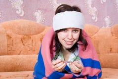 Mädchen, das auf dem Couchkranken mit einem Thermometer liegt Stockfotos