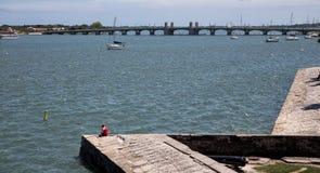 Mädchen, das auf dem Damm übersieht den Jachthafen sich entspannt Lizenzfreies Stockfoto