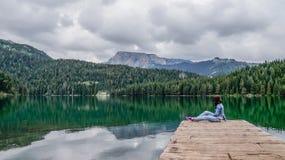 Mädchen, das auf dem Dock des schwarzen Sees im Nationalpark Durmitor sitzt montenegro Stockfotografie