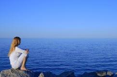 Mädchen, das auf dem Felsen durch das ruhige Meer sitzt Stockbilder