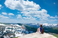 Mädchen, das auf dem Felsen auf dem Wandern von Reise in den schönen Bergen sitzt lizenzfreies stockfoto
