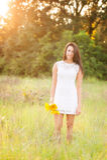 Mädchen, das auf dem Gebiet mit Sonnenblumen steht Stockfoto