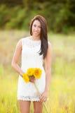 Mädchen, das auf dem Gebiet mit Sonnenblumen steht Stockfotos