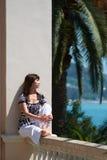 Mädchen, das auf dem Geländer sitzt lizenzfreie stockbilder