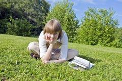 Mädchen, das auf dem Gras liegt Stockfotos