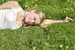 Mädchen, das auf dem Gras liegt Stockbild