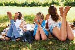 Mädchen, das auf dem Gras mit einem Hund liegt Lizenzfreie Stockfotos