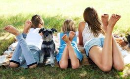 Mädchen, das auf dem Gras mit einem Hund liegt Lizenzfreie Stockbilder