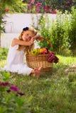 Mädchen, das auf dem Gras mit einem Korb der Frucht sitzt stockbilder