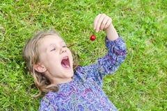 Mädchen, das auf dem Gras mit Kirsche liegt Lizenzfreies Stockbild