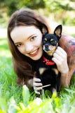 Mädchen, das auf dem Gras nahe bei einem Hund liegt lizenzfreie stockbilder