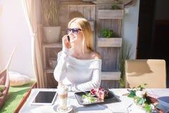 Mädchen, das auf dem Mobile am Café spricht Lizenzfreies Stockfoto