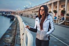 Mädchen, das auf dem Pier im Sonnenuntergang steht stockbild