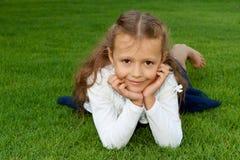 Mädchen, das auf dem Rasen liegt Stockbild