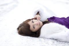 Mädchen, das auf dem Schnee im Kleid liegt Stockfotografie
