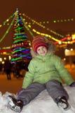Mädchen, das auf dem Schnee und dem Lachen sitzt Stockbild