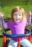 Mädchen, das auf dem Schwingen glücklich im Wiesengraspark schwingt Lizenzfreies Stockfoto