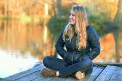 Mädchen, das auf dem See-Ufer sitzt Stockbilder