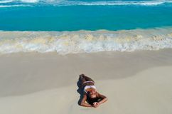 Mädchen, das auf dem Seestrand in einem weißen Bikini liegt stockfotografie