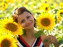 Mädchen, das auf dem Sonnenblumegebiet aufwirft Lizenzfreie Stockbilder