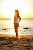 Mädchen, das auf dem Strand in der Schwimmenklage während des Sonnenuntergangs steht stockbilder