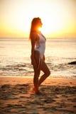 Mädchen, das auf dem Strand in der weißen Schwimmenklage während des Sonnenuntergangs steht lizenzfreie stockfotos