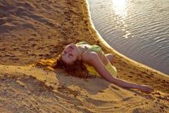 Mädchen, das auf dem Strand liegt Stockfotos